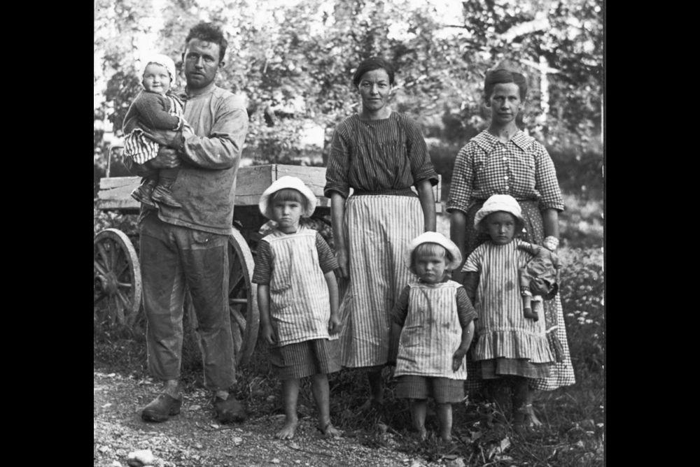 Bakom ryggen på Bo Victorin skymtar en skugga av Sörmlands underutveckling: statare vid Björksund, Tystberga på 1920-talet. Till höger statarhustrun och mjölkerskan Maria Ljungman med enda barnet, dottern Alva, som flyttade runt med familjen från gård till gård de sju första åren av sitt liv. Sen blev de kvar vid Björksund, sannolikt ända tills statsystemet avskaffades på 1940-talet. Övriga personer på bilden okända. Foto: Sörmlands museums arkiv.
